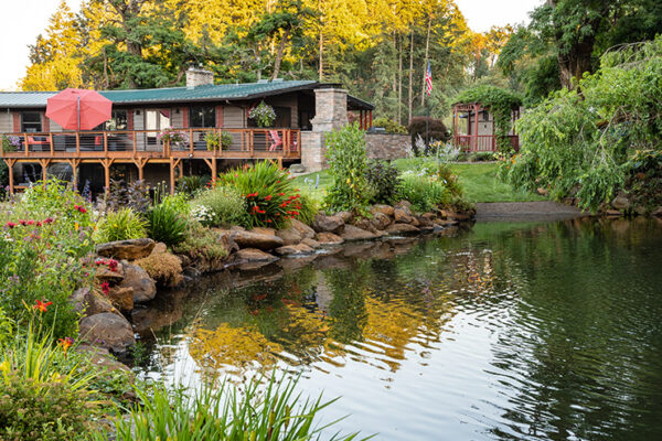 beautiful pond with landscaping surrounding it and a house in the background - landscape design by EarthTech Landscaping Solutions